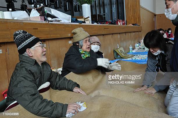 An elderly couple is reunited with relatives at a center for displaced persons in the devastated town of Otsuchi Iwate prefecture on March 18 one...