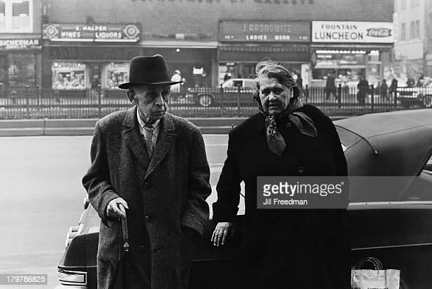 An elderly couple lean against a car on Delancey Street New York City 1966