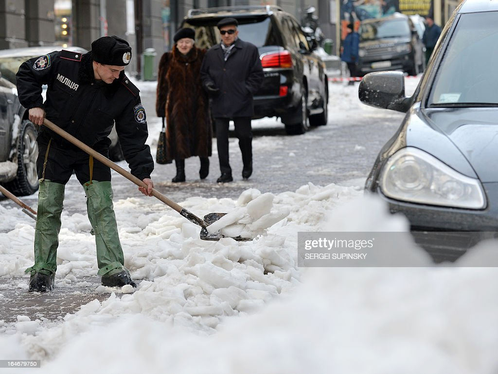 An elderly couple passes policemen clearing snow and ice from a road in the centre of Kiev on March 26, 2013. Police and the military were commandeered to help communal services to clear Kiev streets after record-breaking snow that blanketed the capital and other parts of the country over the weekend. SUPINSKY