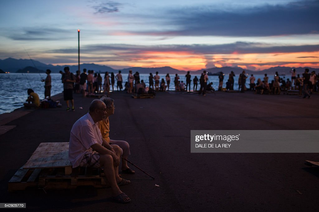 An elderly couple sit on a wooden pallet as people take pictures of the sunset on a public pier in Hong Kong on June 25, 2016. / AFP / DALE