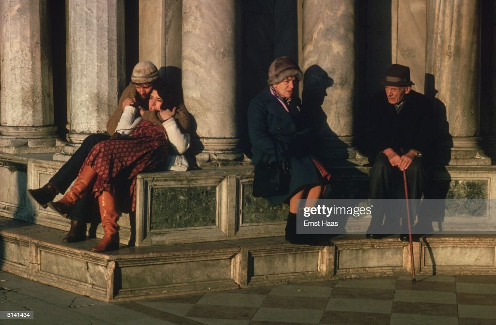 An elderly couple sitting next to a young couple in the Piazza San Marco, Venice. Colour Photography book.