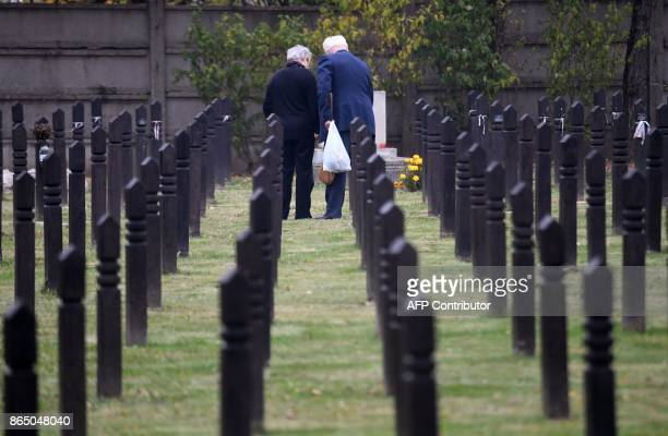 An elderly couple stands amidst graves at the Koztemeto cemetery for the victims of the 1956 uprising against Soviet occupation in Budapest on...