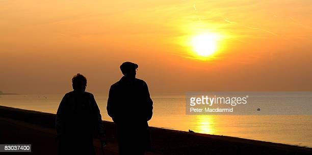 An elderly couple stroll on the sea front in the early morning on September 28 2008 in Hythe England
