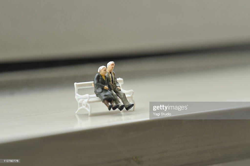 An elderly couple to sit on the bench