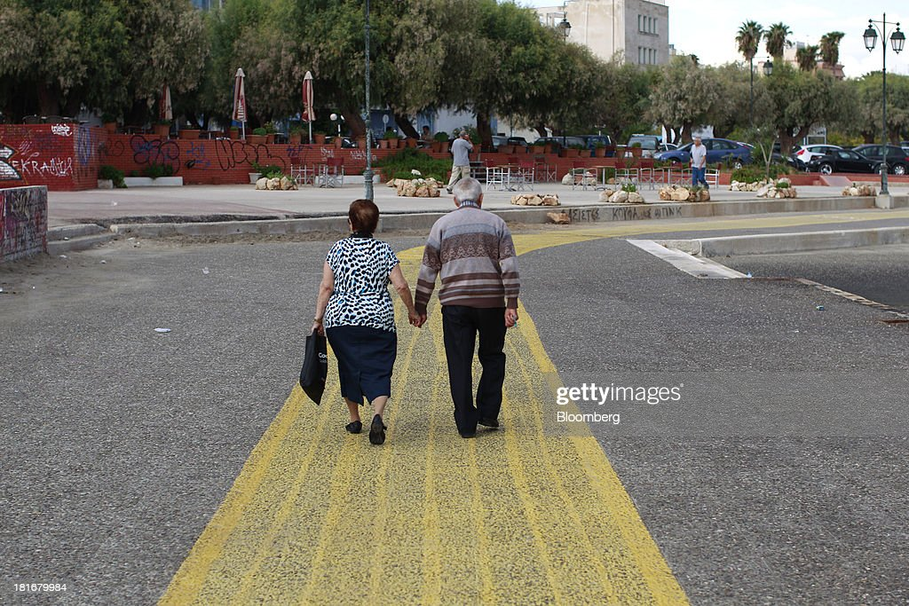 An elderly couple walk along the waterfront in Corinth, Greece, on Monday, Sept. 23, 2013. While the country's lenders are on firmer footing after getting capital from euro-area and International Monetary Fund bailout funds, they still need to reduce the non-performing loans that have tripled to 29 percent of the total in three years and threaten their new-found solvency. Photographer: Kostas Tsironis/Bloomberg via Getty Images