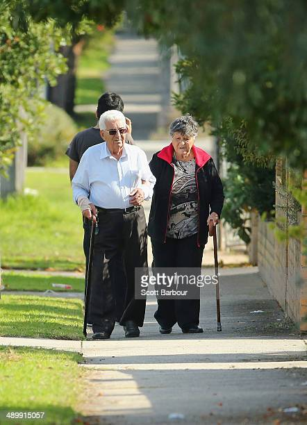 An elderly couple walk down the street on May 13 2014 in Melbourne Australia Tony Abbott's Coalition government will deliver it's first federal...