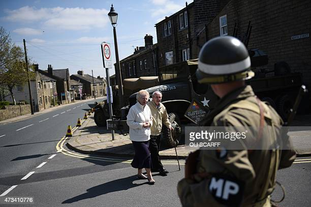 An elderly couple walk past a man dressed as a member of the US military police as he stands guard at a checkpoint on the first day of the Haworth...