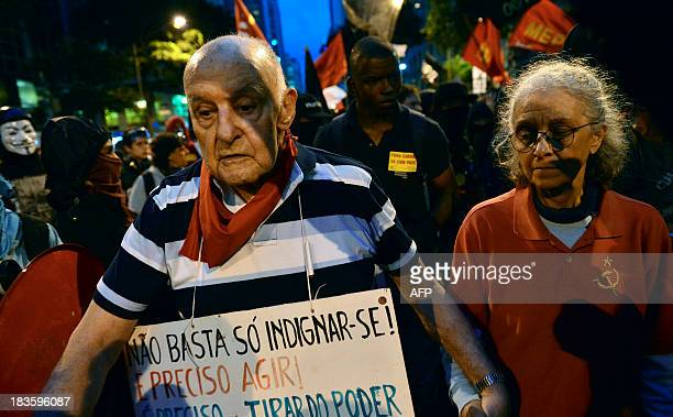 An elderly couple walks during a teachers protest demanding better working conditions and against police beating on October 7 2013 in Rio de Janeiro...
