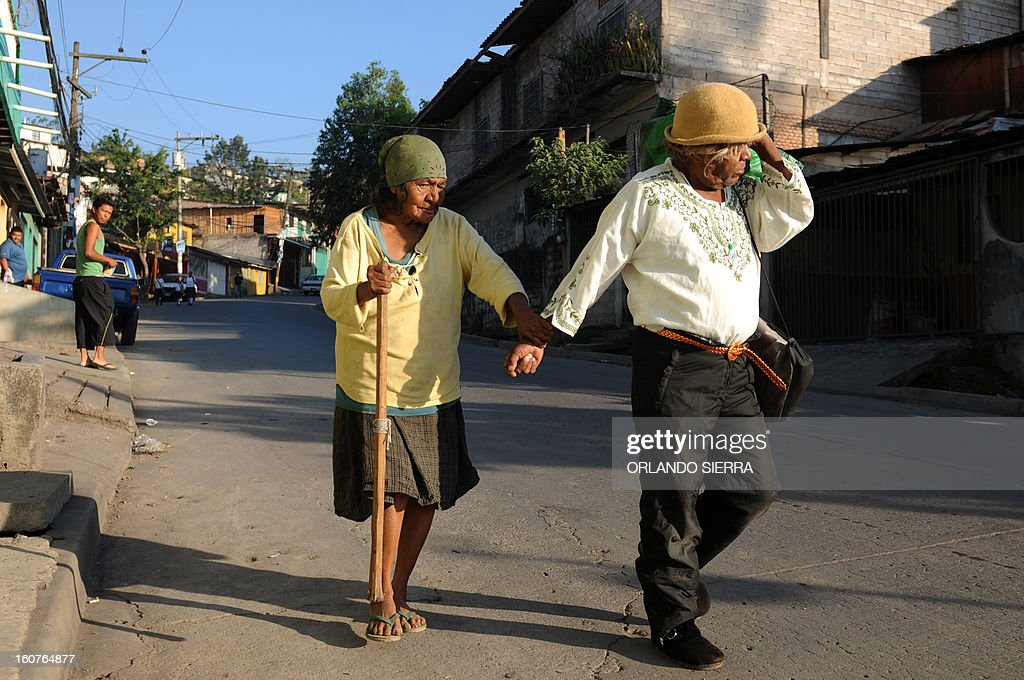 An elderly couple walks hand in hand along a street in a poor neighbourhood of Tegucigalpa on February 5, 2013. Honduras' notorious street gangs, especially the Mara 18 and the Mara 13 or Salvatrucha, have imposed a curfew and are charging a 'war tax' in some of the capital's poorest sectors -- thing which led the police to deploy more personnel in theses areas. The violent maras are active in murders, extorsion, drug dealing, arms trafficking and other crimes. The United Nations says Honduras, a country plagued by powerful street gangs and drug-related violence, has the world's highest homicide rate. In 2010 it was 82 per 100,000 inhabitants, and rose to 86 in 2011. By comparison, in drug-cartel-plagued Mexico, for instance, the rate was about 18 in 2010. AFP PHOTO/Orlando SIERRA