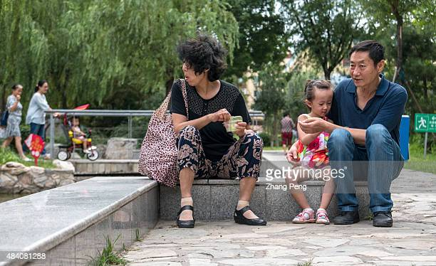 An elderly couple who left their hometown to live in Beijing takes care of their only grandchild playing in their residential community China is...