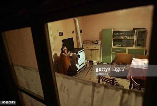 An elderly Croatian Neda Milanovic warms herself near the stove as temperatures fall below minus 15 degrees Celsius in the village of Darda close to...
