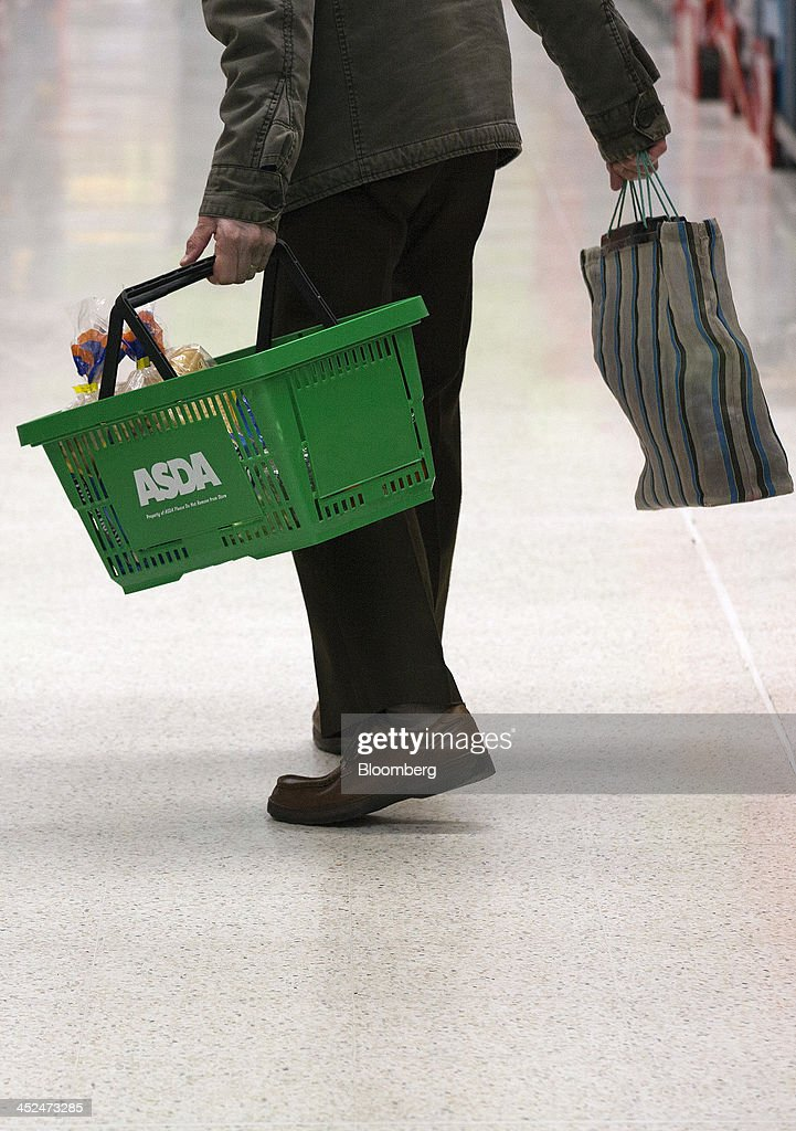 An elderly customer carries his groceries in a branded shopping basket as he shops for goods inside an Asda supermarket in Wembley, London, U.K., on Friday, Nov. 29, 2013. Britons queued outside Asda supermarkets this morning and charged into stores when doors opened at 8 a.m. as the U.K. grocery chain took on the Black Friday mantle from U.S. owner Wal-Mart Stores Inc. Photographer: Simon Dawson/Bloomberg via Getty Images