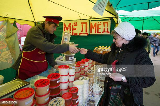 An elderly customer hands over ruble banknotes as she buys a pot of honey at an open air street market stall in Moscow Russia on Saturday April 18...