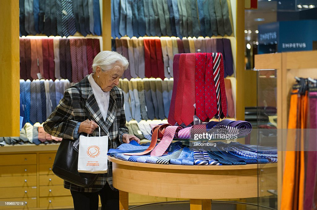 An elderly customer inspects a dispay of men's ties inside an El Corte Ingles SA department store in Barcelona, Spain, on Thursday, May 30, 2013. Spain's recession eased in the first quarter as domestic demand stabilized while exports, which the government says will drive the recovery of the euro-area's fourth-largest economy, fell at the fastest pace in a year. Photographer: David Ramos/Bloomberg via Getty Images