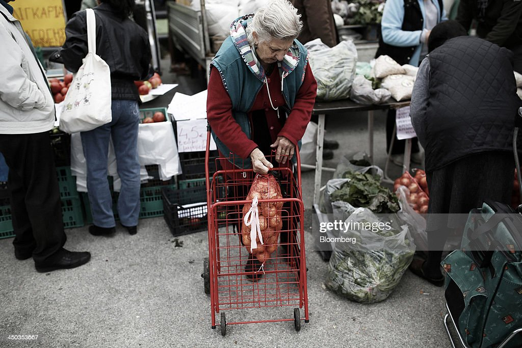 An elderly customer lowers a sack of onions into a trolley after purchasing them at a farmers' market in Thessaloniki, Greece, on Saturday, Nov. 16, 2013. Greek Prime Minister Antonis Samaras, who survived a no-confidence vote on Nov. 11 with his parliamentary majority reduced to four, is trumpeting the first economic growth in seven years for 2014. Photographer: Konstantinos Tsakalidis/Bloomberg via Getty Images