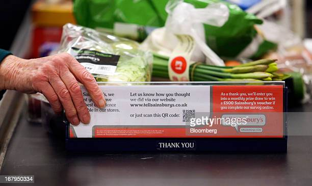 An elderly customer places a shopping divider onto a conveyor belt at a checkout counter at a Sainsbury's supermarket store operated by J Sainsbury...