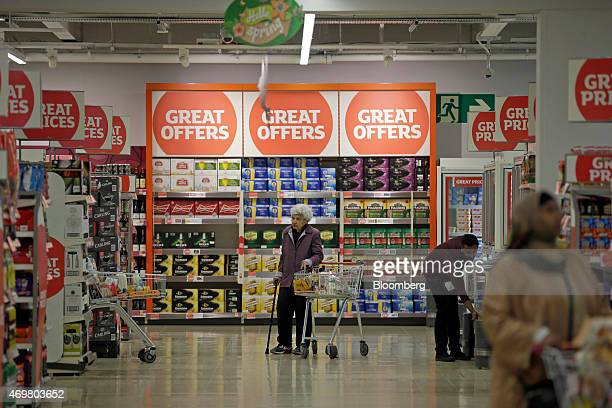 An elderly customer pushes her shopping cart beneath promotional signs offering 'great prices' as she browses for goods inside a Sainsbury's...