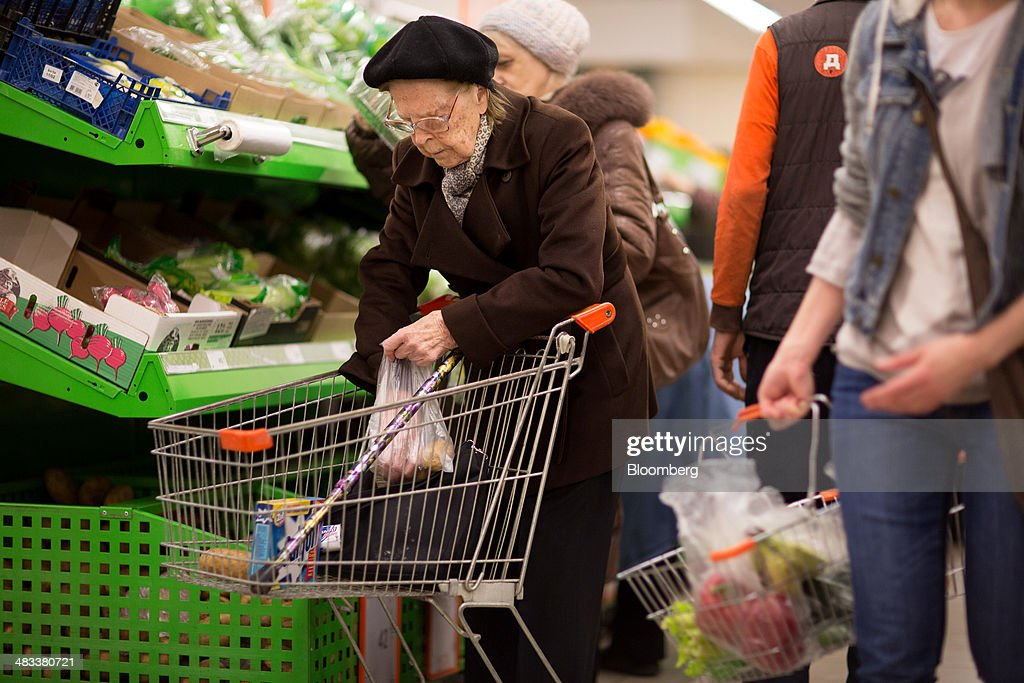 An elderly customer selects fresh vegetables for her shopping cart inside a Dixy supermarket operated by OAO Dixy Group in Moscow, Russia, on Tuesday, April 8, 2014. Suppliers suffering from ruble depreciation this quarter are urging retailers to increase prices. Photographer: Andrey Rudakov/Bloomberg via Getty Images