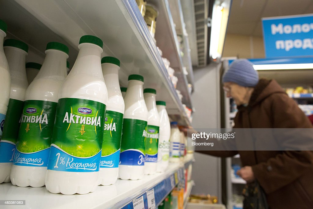 An elderly customer selects products from a shelf beside a display of Danone SA Activia Kefir yoghurt products inside a Dixy supermarket operated by OAO Dixy Group in Moscow, Russia, on Tuesday, April 8, 2014. Suppliers suffering from ruble depreciation this quarter are urging retailers to increase prices. Photographer: Andrey Rudakov/Bloomberg via Getty Images