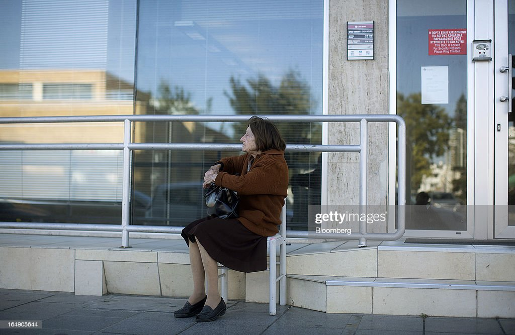 An elderly customer sits and waits for a branch of a Cyprus Popular Bank Pcl, also known as Laiki Bank, to open in Nicosia, Cyprus, on Friday, March 29, 2013. Cypriots face a second day of bank controls over their use of the euro as officials in Europe urged the country to move quickly to lift the restrictions, the first time they have been imposed on the common currency. Photographer: Simon Dawson/Bloomberg via Getty Images