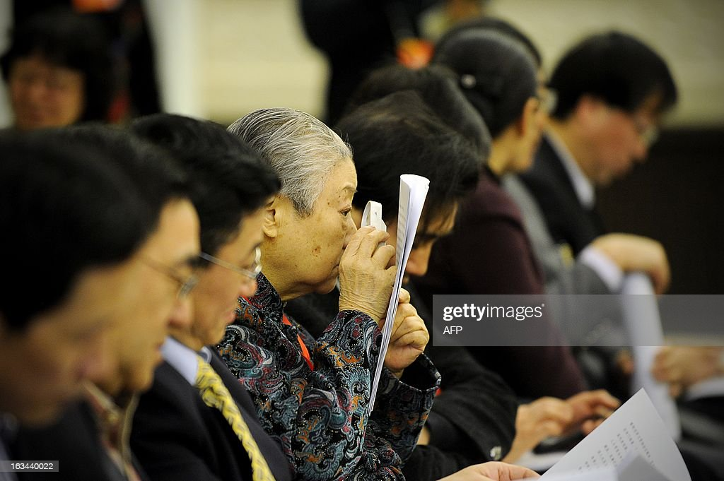 An elderly delegate (C) reads a report with a magnifying glass during the National People's Congress (NPC) at the Great Hall of the People in Beijing on March 10, 2013. Thousands of delegates from across China were meeting this week to seal a power transfer to new leaders whose first months running the Communist Party have pumped up expectations with a deluge of propaganda.