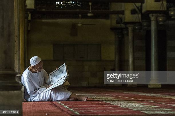 An elderly Egyptian man reads a copy of the Koran Islam's holy book after the Friday weekly prayer at alAzhar mosque in the capital Cairo's Islamic...