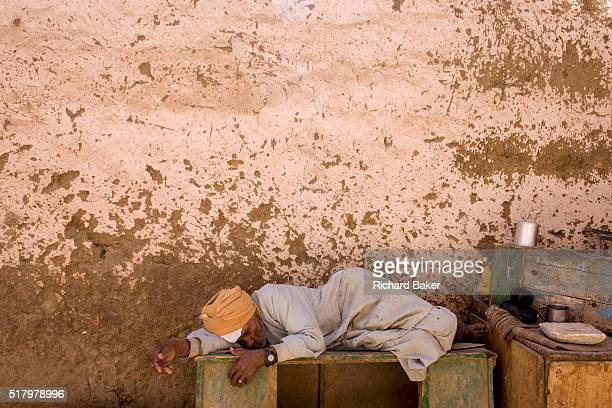 An elderly Egyptian sleeps in the midday shade of a mudsplattered wall in the village of Bairat on the West Bank of Luxor Nile Valley Egypt Stretched...