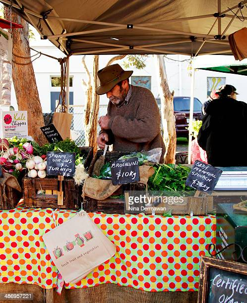 An elderly farmer manning his certified organic vegetable stall at the Farmers Market