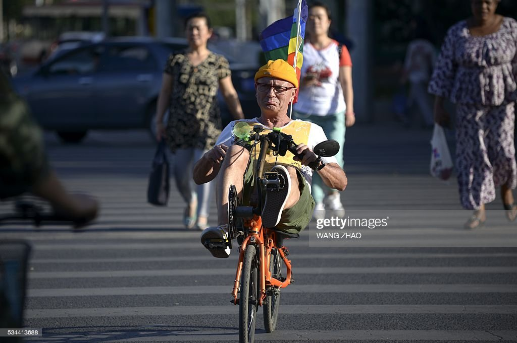An elderly foreign man rides a bicycle across a street in Beijing on May 26, 2016. / AFP / WANG