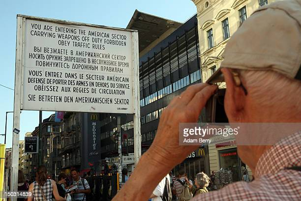 An elderly French tourist photographs the 'You Are Entering the American Sector' sign at Checkpoint Charlie on August 15 2012 in Berlin Germany In...