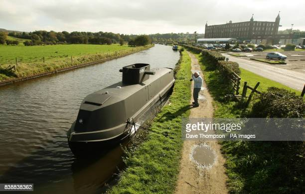An elderly gentleman takes a photograph of a canal barge transformed into a replica of a German UBoat on the LeedsLiverpool canal in Botonay Bar near...