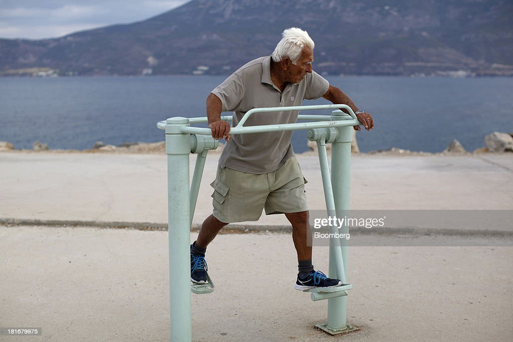 An elderly Greek man works out on an exercise machine on the beach in Corinth, Greece, on Monday, Sept. 23, 2013. While the country's lenders are on firmer footing after getting capital from euro-area and International Monetary Fund bailout funds, they still need to reduce the non-performing loans that have tripled to 29 percent of the total in three years and threaten their new-found solvency. Photographer: Kostas Tsironis/Bloomberg via Getty Images