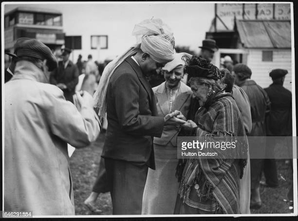 An elderly gypsy fortuneteller reads the palm of a visitor to the races at Epsom Surrey   Location The Downs Epsom Surrey England UK