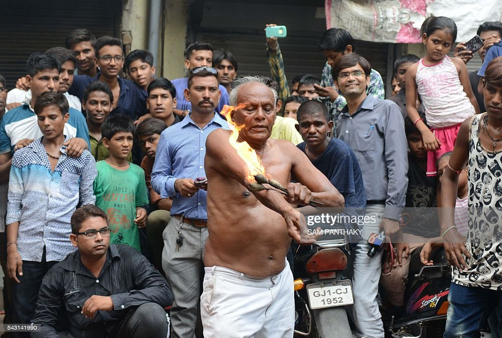An elderly Hindu devotee rubs fire on his body during a rehearsal for the forthcoming annual Rathyatra festival in Ahmedabad on June 26, 2016. The annual Rathyatra festival is scheduled to take place on July 6, 2016. / AFP / SAM