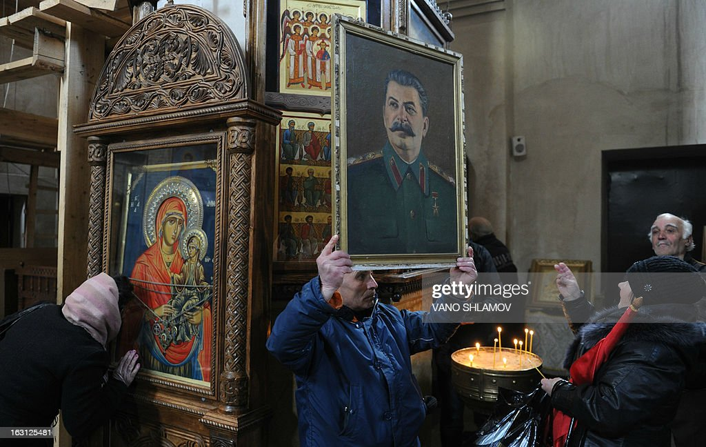 An elderly holds a portrait of Soviet dictator Joseph Stalin inside a church in Stalin's native town of Gori, some 80 km from the capital Tbilisi, on March 5, 2013, during ceremonies to mark the 60th anniversary of Stalin's death. Russia marks today 60 years since the death of Stalin with attitudes split about whether to view him as a tyrant who slaughtered millions or a national saviour who helped turn the country into a global superpower that emerged victorious in World War II.