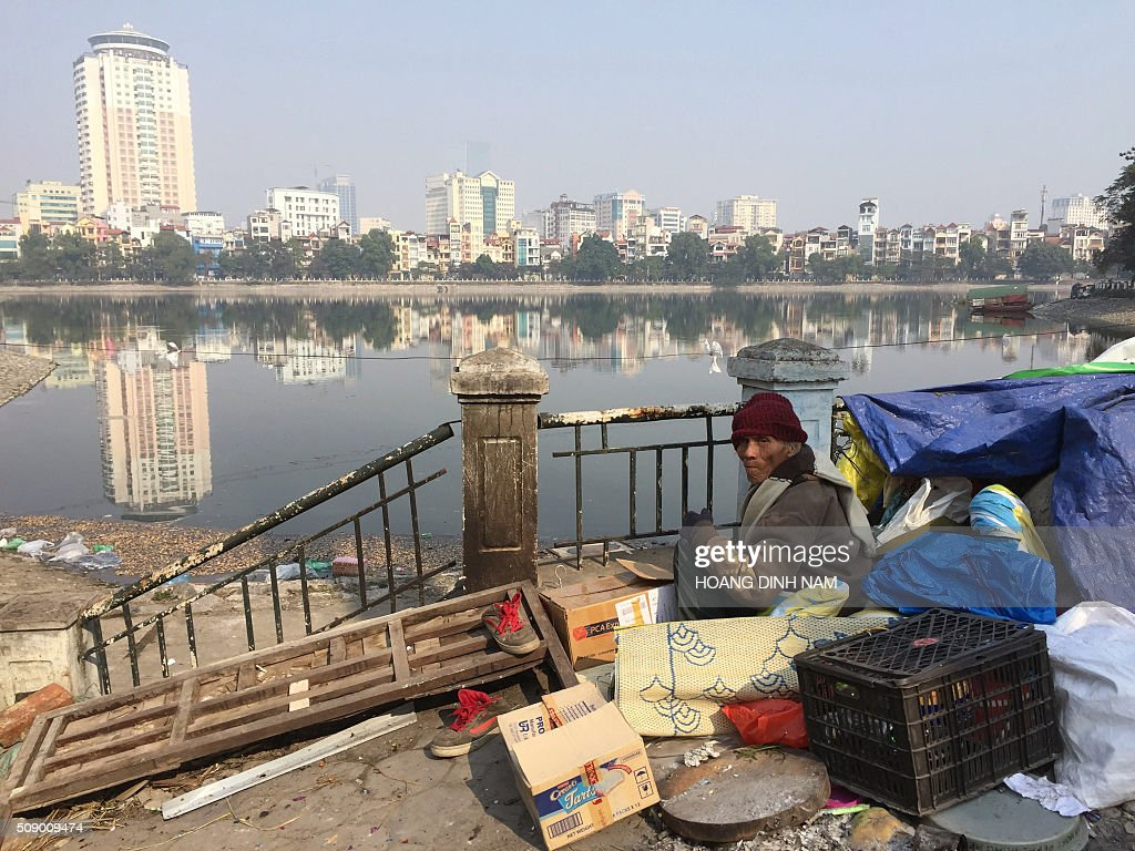 An elderly homeless man wakes up at his open-air makeshift refuge next to a lake in downtown Hanoi on February 8, 2016 as Vietnamese people celebrate the Lunar New Year or Tet. Vietnamese mark the Lunar New Year, this year the Year of the Monkey in the Chinese Zodiac, along with many countries in east Asia. AFP PHOTO / HOANG DINH Nam / AFP / HOANG DINH NAM