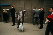 An elderly homeless man walks slowly past a Barclays Bank cash dispenser at which business people are either queueing or typing in their PIN numbers...
