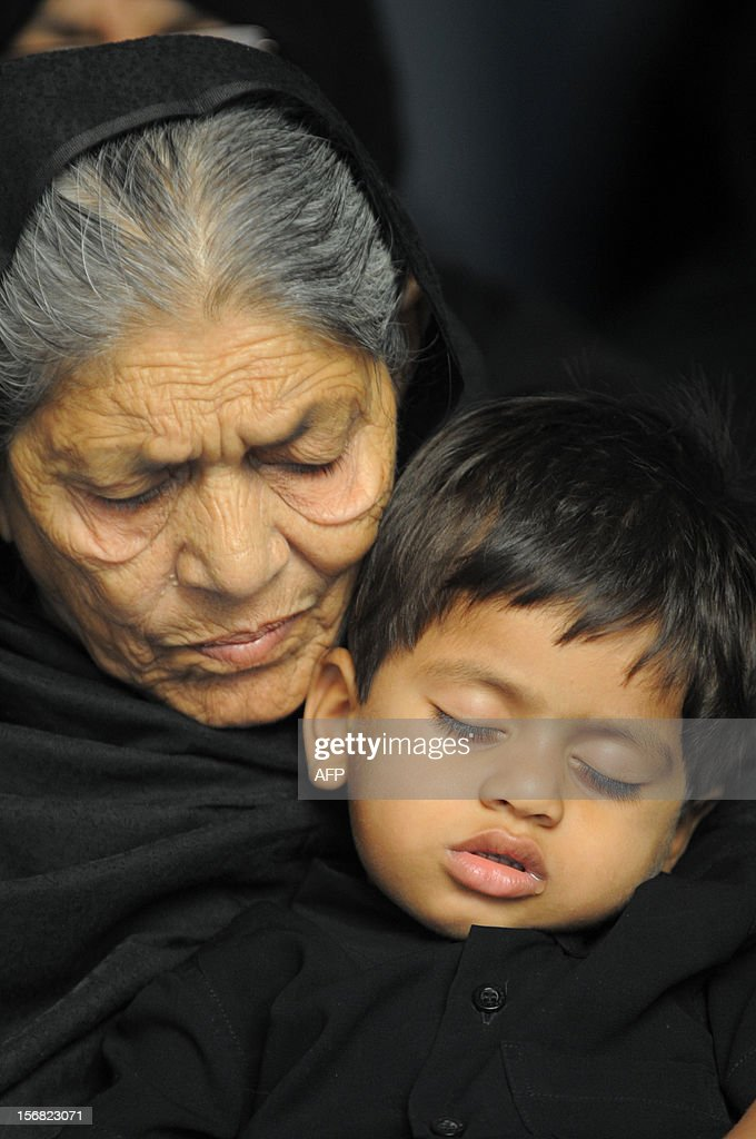 An elderly Indian devotee holds a child as Shiite Muslims perform ritual acts of self flagelation with a cluster of knives and chains during a religious procession in Ahmedabad on November 22, 2012. Rituals are held on the seventh day of Moharram, which commemorates the seventh century slaying of the Prophet Mohammed's grandson in southern Iraq. During the holy month of Muharram, large processions are formed and the devotees parade the streets holding banners and carrying models of the mausoleum of Hazrat Imam Hussain and his people, who fell at Karbala. Muslims show their grief and sorrow by inflicting wounds on their own bodies with sharp metal tied to chain with which they scourge themselves, in order to depict the sufferings of the martyrs AFP PHOTO / Sam PANTHAKY