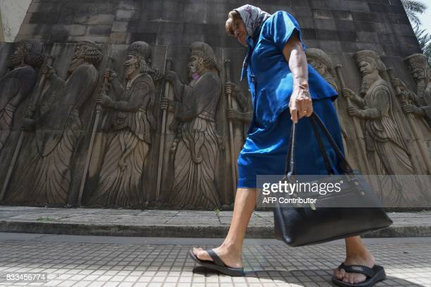 An elderly Indian Parsi woman walks past relief figures of knights at a Fire Temple during Navroze the Parsi New Year in Mumbai on August 17 2017...