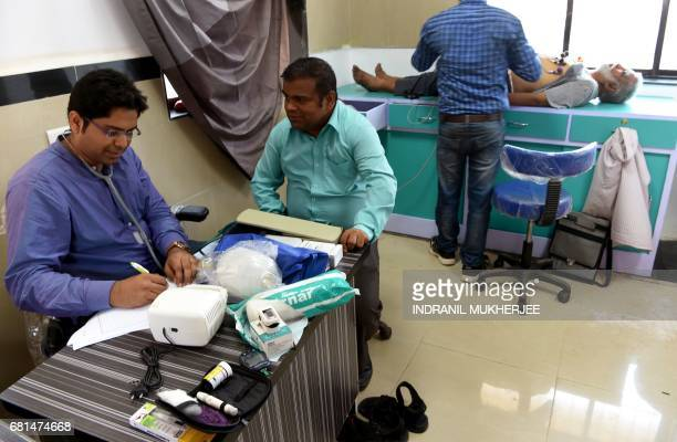 An elderly Indian patient receives an Electrocardiograph inside a 'One Rupee Clinic' as another patient has a presciption written in an emergency...