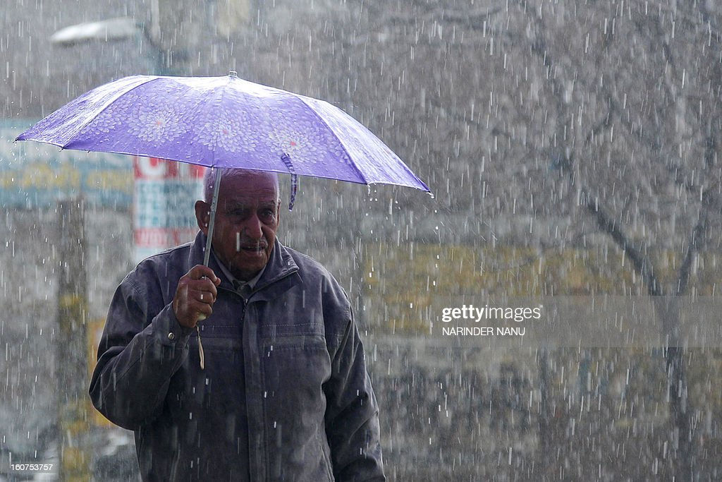 An elderly Indian pedestrian walks through heavy rains in Amritsar on February 5, 2013. With moderate to heavy rains lashing the northern region, farm experts today warned of damage to wheat crop if downpour accompanied with high speed winds prolongs for next couple of days. AFP PHOTO/ NARINDER NANU
