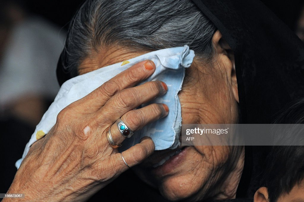 An elderly Indian woman reacts as Shiite Muslims perform ritual self flagelation acta with a cluster of knives and chains during a religious procession in Ahmedabad on November 22, 2012. Rituals are held on the seventh day of Moharram, which commemorates the seventh century slaying of the Prophet Mohammed's grandson in southern Iraq. During the holy month of Muharram, large processions are formed and the devotees parade the streets holding banners and carrying models of the mausoleum of Hazrat Imam Hussain and his people, who fell at Karbala. Muslims show their grief and sorrow by inflicting wounds on their own bodies with sharp metal tied to chain with which they scourge themselves, in order to depict the sufferings of the martyrs AFP PHOTO / Sam PANTHAKY