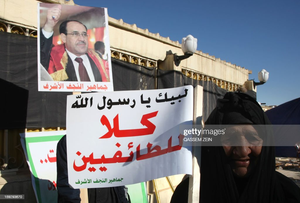 An elderly Iraqi woman holds a sign reading in Arabic, 'no the sectarianism', during a demonstration against sectarianism in the Shiite shrine city of Najaf on January 11, 2013. There have been continued protests in Iraq's Sunni-majority areas calling for the release of prisoners and criticising Prime Minister Nuri al-Maliki's Shiite-led government.
