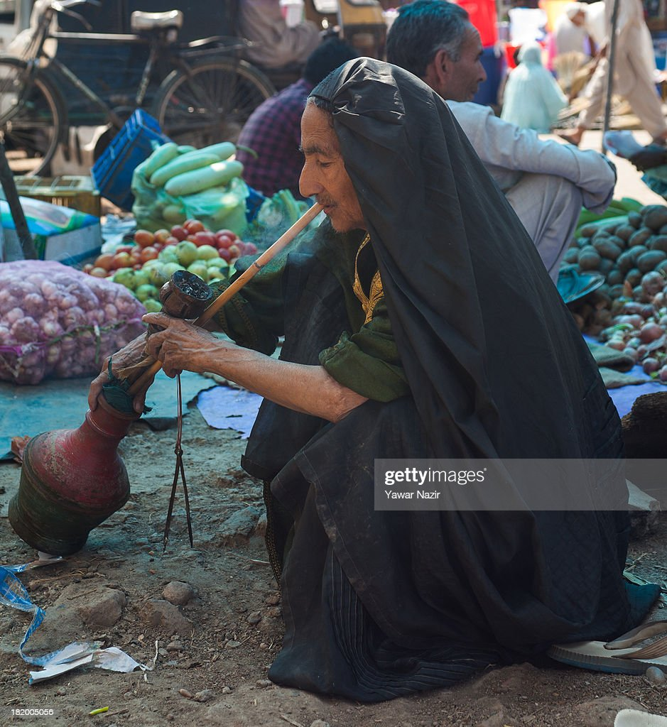 An elderly kashmir Muslim woman wearing a Burka (veil ) smokes a hookah in a market on September 27, 2013 in Srinagar, the summer capital of Indian administered Kashmir, India. Also known as Jajeer, Hookahs have gone out of fashion in Kashmir during the recent years due to increasing consumption of cigarettes.