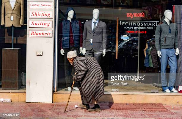 An elderly Kashmiri beggar walks in front a shop on November 06 2017 in Srinagar the summer capital of Indian administered Kashmir India Markets in...