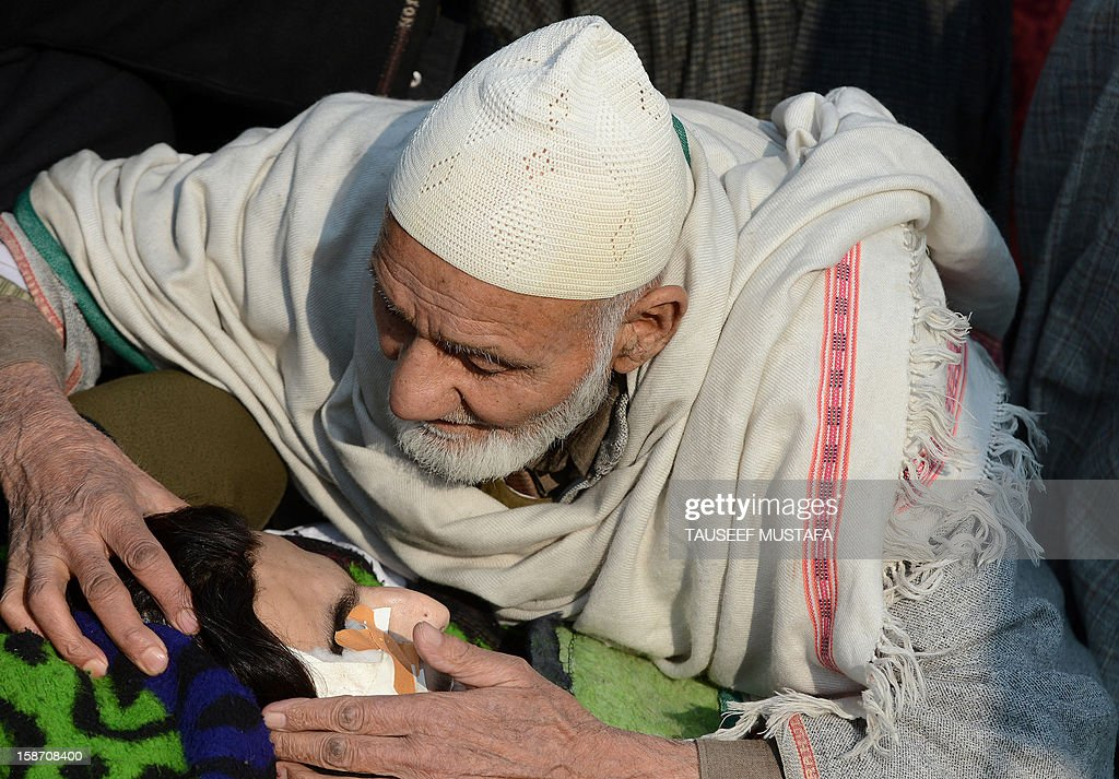 An elderly Kashmiri mourner embraces the body of alleged Pakistan-based Lashker-e-Toiba militant Mudasir Sheikh alias Mavia a self styled 'district commander' kisses his body during the funeral of him and his Pakistani associate Tamim in Kulgam district of south Kashmir some 75kms from Srinagar on December 25, 2012. Security forces confronted the pair of rebels and in the ensuing gunbattle they and a policeman were killed. A police spokesman said that the two were implicated in an attack on The Silver Star Hotel in Srinagar and on an army convoy. AFP PHOTO/Tauseef MUSTAFA