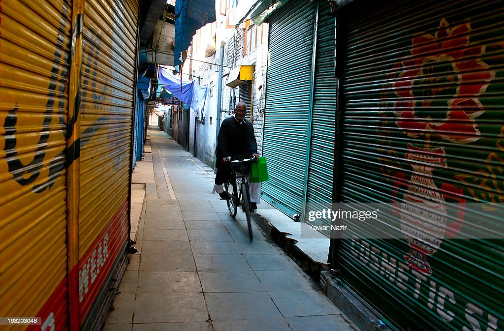 An elderly Kashmiri Muslim man rides a cycle next the the closed shops during a curfew like restriction on March 06, 2013 in Srinagar, the summer capital of Indian Administered Kashmir, India. Indian authorities imposed curfew like restrictions in most parts of Kashmir following a killing of kashmiri youth by Indian army in North Kashmir's Baramulla district yesterday.