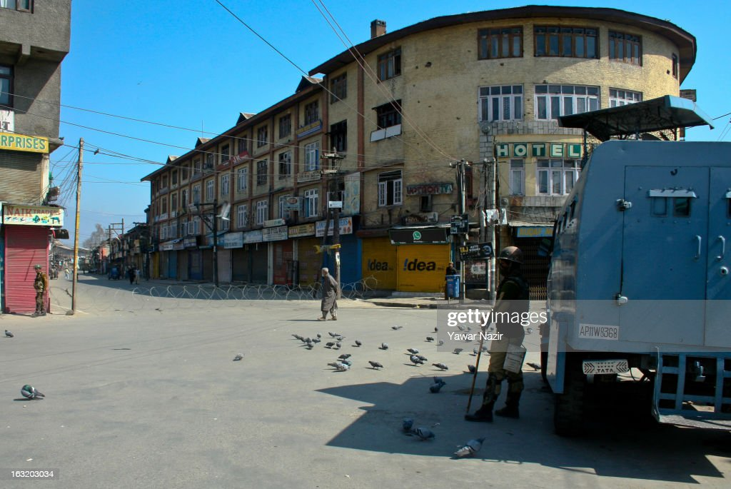An elderly Kashmiri Muslim man walks as Indian paramilitary forces stand guard during a curfew like restriction on March 06, 2013 in Srinagar, the summer capital of Indian Administered Kashmir, India. Indian authorities imposed curfew like restrictions in most parts of Kashmir following a killing of kashmiri youth by Indian army in North Kashmir's Baramulla district yesterday.