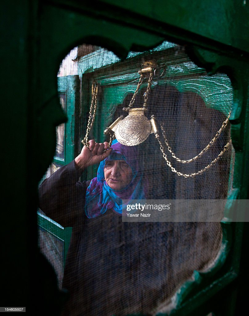 An elderly Kashmiri Muslim woman touches the chain engraved with Quranic verses at the entrance of the shrine of Khaniqahi mullah during a festival on October 23, 2012 in Srinagar, the summer capital of Indian administered Kashmir, India. Thousands of Muslims thronged to the shrine of Mir Syed Ali Hamadan to commemorate the anniversary of the death of the Sufi saint, Hamadan. He is believed to be responsible for the spread of Islam in Kashmir. The shrine gains a special significance on 6th of Zilhaj (last month of Muslim calendar), the death anniversary of Mir Syed Ali Hamadan. On this day, devotees visit the shrine in large numbers to pay a tribute to saint Hamadan.
