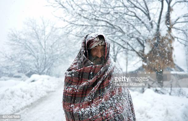TOPSHOT An elderly Kashmiri villager walks through snow in Gund some 70km northeast from Srinagar on January 25 2017 Avalanches killed five people in...